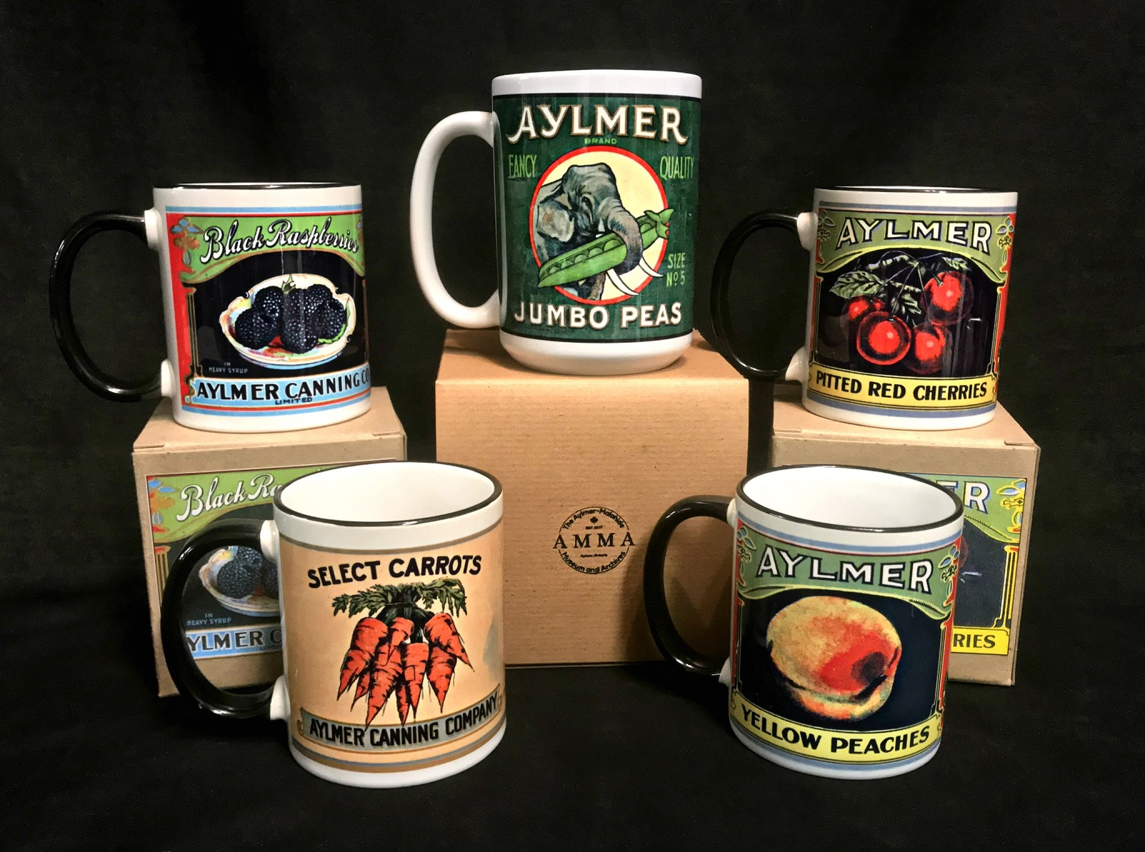 Image of all five variations of the Aylmer Canning Company mugs for sale at the Aylmer Museum.