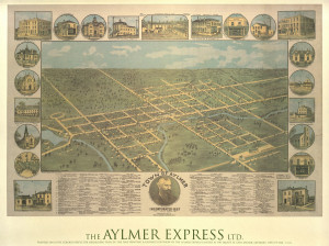 Image of the map of the town of Aylmer for sale at the Aylmer Museum. Depicts a bird's eye view of the town, and has images of various buildings around town at the border.